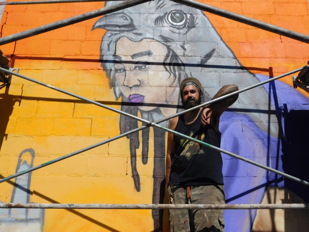 Gainesville artists Ras Justo Luis Rodriguez continues working on his mural of a mockingbird girl.