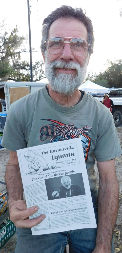 Publisher Joe Courter holds up the latest issue of the Gainesville Iguana.
