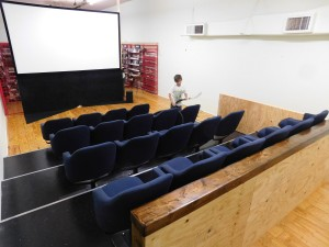 Joe McNeal vacuums the Cyclops Cinema Screening Room, featuring a large digital projection screen.