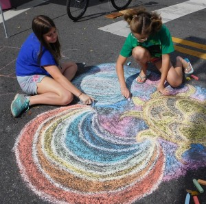 A pair of youngsters express themselves artistically with chalk at the intersection of University and Main.