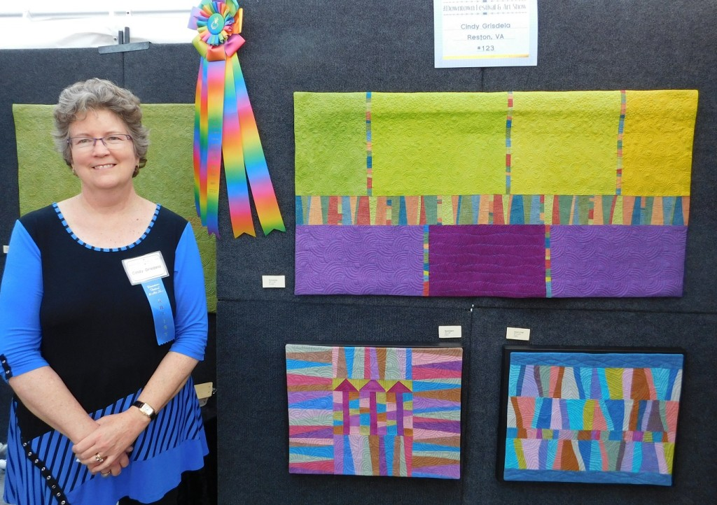 "Cindy Grisdela poses with her Best In Show ribbon and her paintings titled ""Promenade,"" top, ""Skyscrapers,"" left, and ""Waters Edge."""