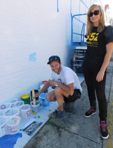 Street artist Franco Fasoli JAZ poses with 352walls curator Iryna Kanishcheva as he begins painting his mural on the Shadow Health wall.