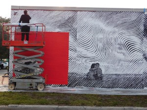 Andrew Antonaccio applies finishing touches to the mural he created with
