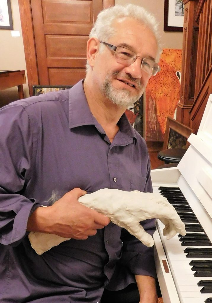 Gerard Bencen, owner of the DNA by the Hand of Man Gallery, gets a helping hand at the piano. Photo by Gainesville Downtown)