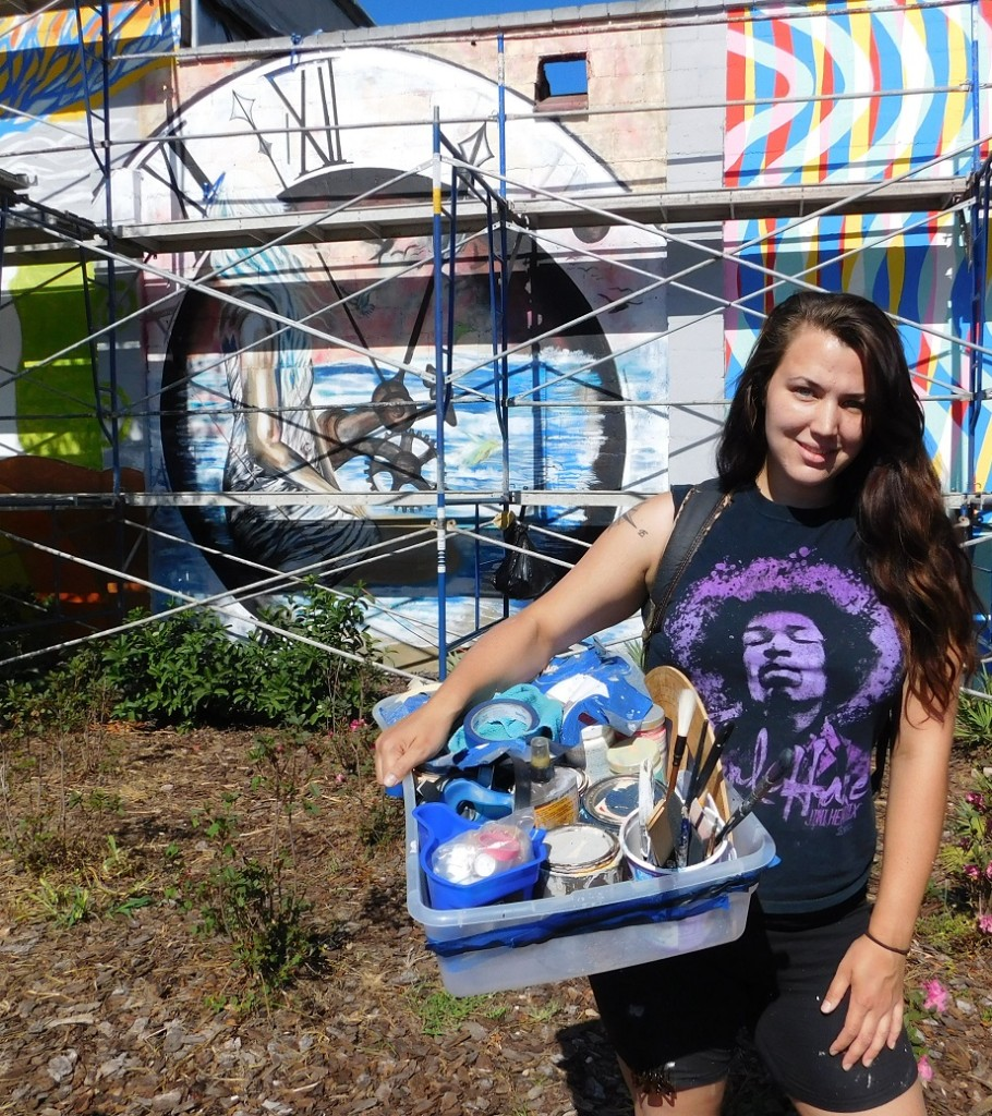 Former Gainesville resident Rachel Sommer, who now resides in Australia, poses in front of her time-themed mural on the old Discount Hi-Fi building.