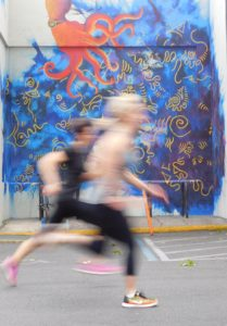 Runners from Alter Ego Fitness blur past the new mural