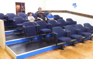 Jason McNeal and sons Joe and Jack check out the seating inside Cyclops Cinemas screening room.
