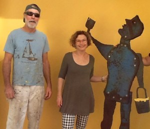 """Local painter Milan Hooper, left, and Nava Ottenberg in front of """"The Painter"""" by Hooper. Photo courtesy of Nava Ottenberg)"""
