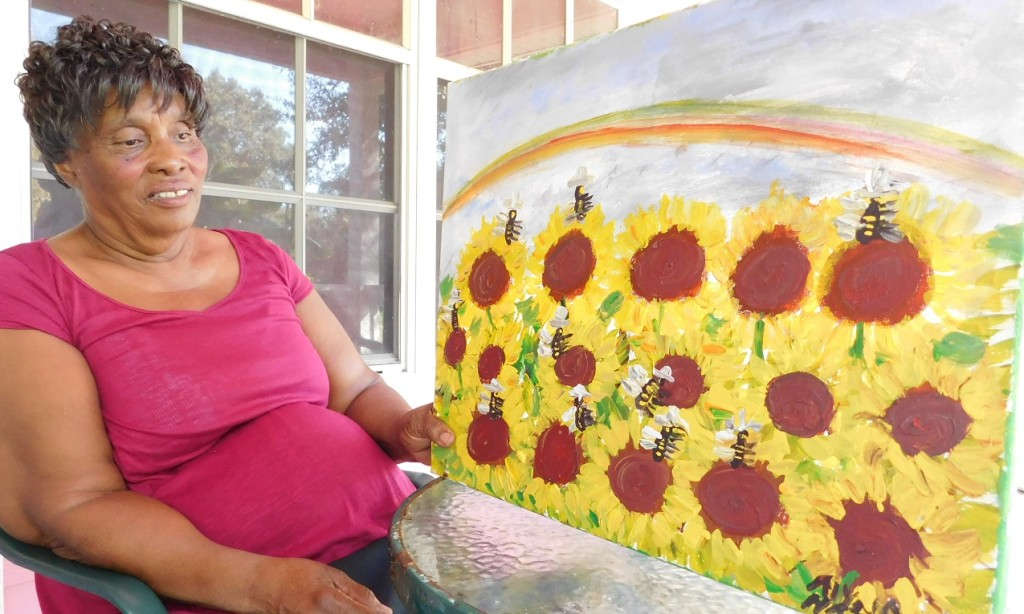 Alyne Harris displays a painting of sunflowers and bumblebees underneath a rainbow.