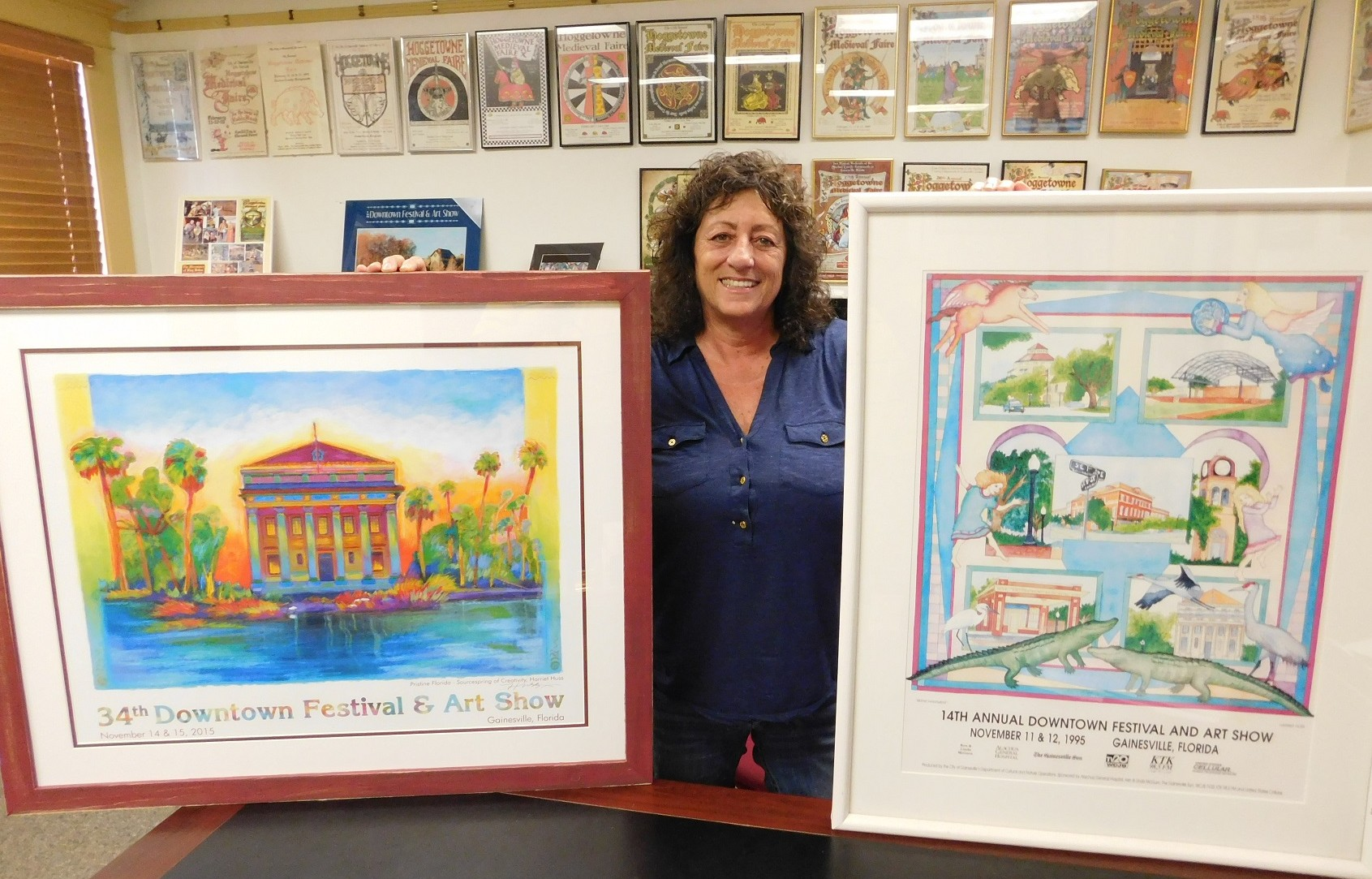Linda Piper displays two Festival posters by Harriet Huss, one from this year and one from 1995.