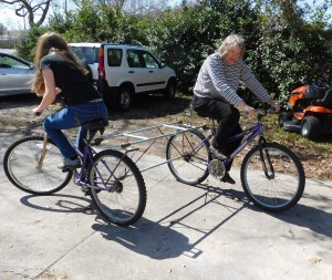 """Flo Turcotte, right, and Lorraine Duerden try to figure out how to best operate the """"push-me, pull-me"""" bike."""