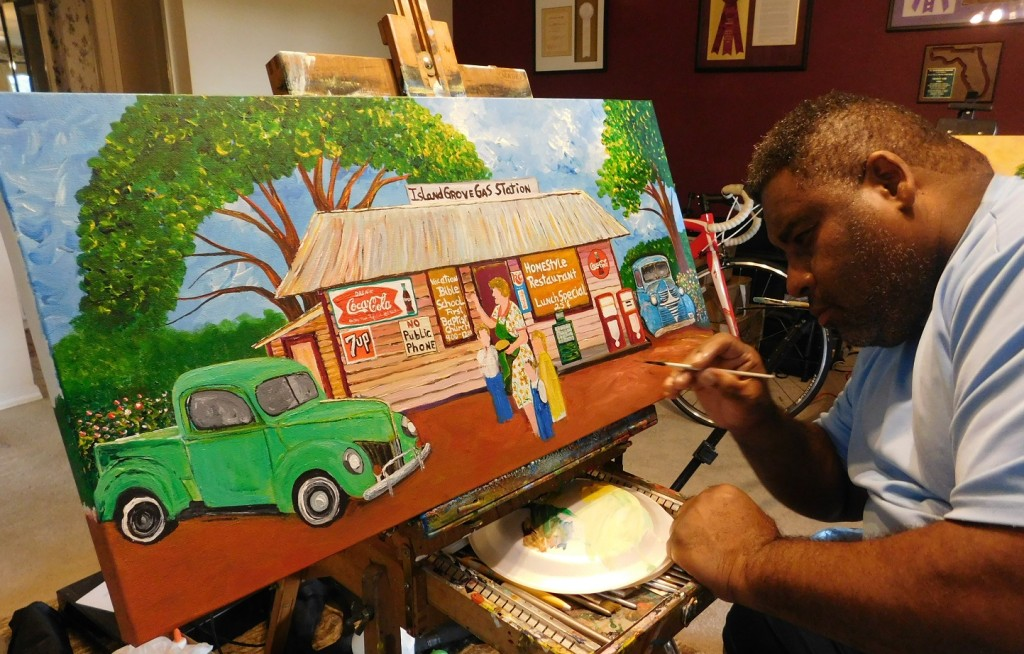 Ernest Lee works on his painting of the Island Grove gas station for Diane Adams. Photo by Gainesville Downtown)