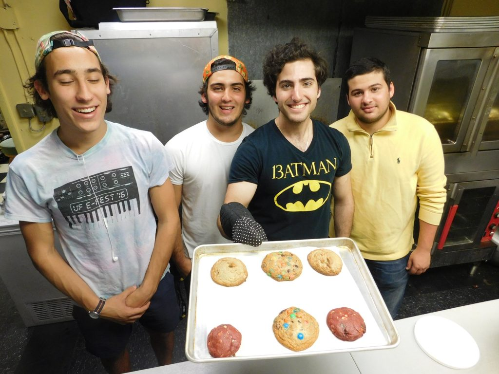 Daniel Leal (holding tray) and crewmembers, from left, Daniel Gavrilin, 19, Roberto Giorgetti, 18, and Samuel Benarroch, 20, in the Cookiegazm kitchen at Omi's.