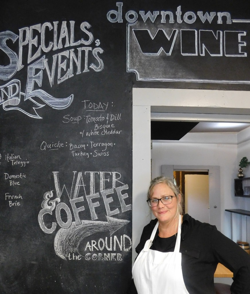 Downtown Wine Cheese owner Maude Wilson in front of her menu board that is updated daily. Photos by Gainesville Downtown)