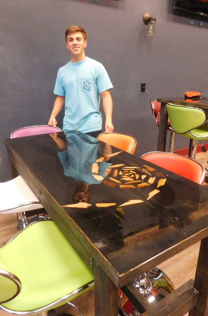 Ryan Roth, Elixirs interim manager and an Alpha Tao Omega fraternity member, shows off a tabletop designed by Alexis Dold.