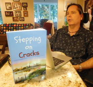 "Hugh E. Suggs and his self-published novel, ""Stepping on Cracks."" Photo by Raphael Michael/Gainesville downtown)"