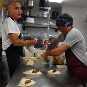 Anthony Campanaro, left, helps Nicholas Iannelli prep tamales. Photo by Gainesville Downtown)